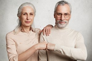 Mature beautiful woman and handsome bearded man express agreement, touch fists, isolated over white concrete background. Grandparents have good relationship, agree with something. Family and pension