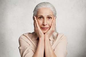 Headshot of elderly beautiful woman with grey hair, make up, keeps hands on cheeks, tries to hide her wrinkled skin, isolated over white concrete wall. People, age, beauty and pension concept