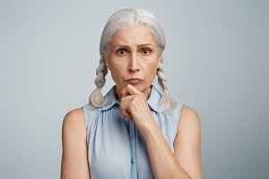 Portrait of serious mature experienced female model with grey hair, wears blouse, keeps hand on chin, has wise expression, isolated over light blue background. People, age and pension concept
