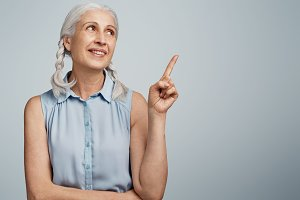 Positive pretty female retiree with wrinkled skin and make up, wears elegant blue blouse indicates at blank copy space for your advertising content. Pleased mature woman advertizes something