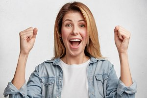 Happy successful young female student rejoices high results on exam, raises fists as shows her big fortune, feels like winner, exclaims joyfully, isolated over white concrete studio background.