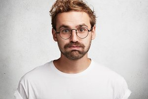Portrait of tired stylish bearded intelligent male student gives deep sigh, presses lips, feels relief after passed exam, isolated over white background. Handsome young unshaven man poses indoor.
