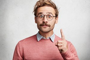 Handsome bearded man has trendy hairdo and mustache raises fore finger as gets good idea, has intriguing and clever expression, expresses his confidence, isolated over white concrete background