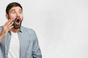 Horizontal studio shot of shocked frightened male model has hush reaction as sees his phobia, keeps mouth opened, dressed casually, isolated over white background with copy space for your text