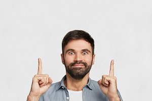 Studio shot of cheerful excited bearded stylish male has dark thick beard and mustache, dressed casually, indicates with index fingers upwards at blank copy space for your advertising content
