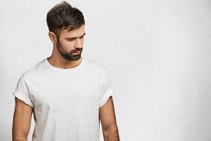 Sporty muscular man with trnedy hairdo, beard and mustache, wears white t shirt, looks with dreamy expression down, isolated over white concrete wall with copy space for your advrtisment or hearder