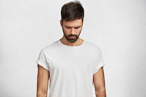 Handsome brunet male with trendy hairdo, has muscular body, wears caual white t shirt, looks down as notices something on floor, poses against concrete background. Attractive man hangs head.