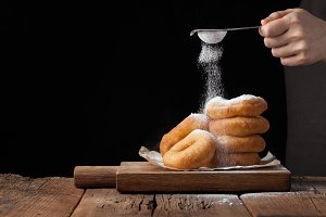 Baker sprinkles sweet donuts with powder sugar on black background. Delicious, but unhealthy food on the old wooden table with copy space