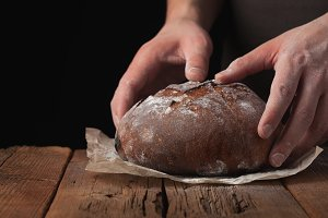 Closeup of male hands put fresh bread on an old rustic table on black background with copy space for your text
