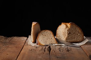 Sliced delicious fresh bread on black background with copy space for your text. The loaf on the old rustic table
