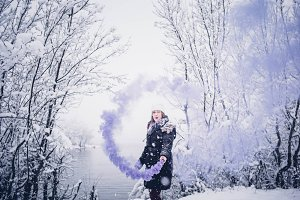 Girl in snow blue smoke bomb.