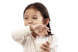 Preschool girl holding a glass with