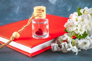 Red heart in a small glass jar on a gray concrete background. The concept of Valentine's Day. A symbol of love.