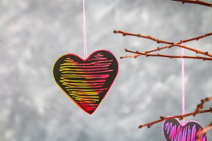 Black-pink hearts hang on branches on a gray concrete background. Love tree. The concept of Valentine's Day. A symbol of love.
