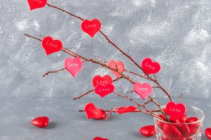 Red hearts with an inscription Love hang on branches on a gray concrete background. Love tree. The concept of Valentine's Day. A symbol of love.
