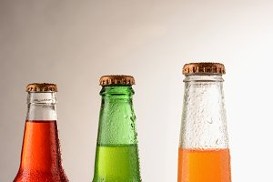 Three different soda bottles covered
