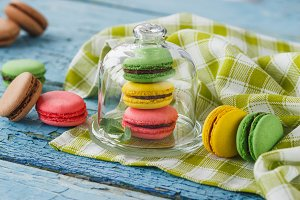 Green, pink, brown and yellow french macarons with mint leaves