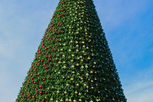 City Christmas tree decorated with colorful balls and garlands.
