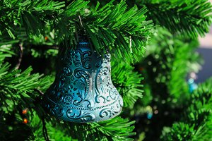 Toy bell on a Christmas tree. Element of the New Year's holiday.