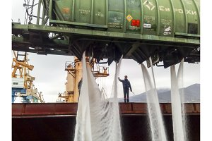 spillage of saltpeter from the car into the hold of the tanker. Loading of mineral fertilizers in the ship's hold.