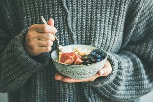 Woman in grey woolen sweater eating rice coconut porridge