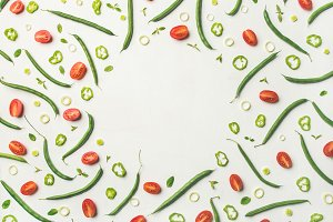 Flat-lay of fresh vegetable slices over white background, food frame