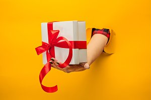 close-up of female hand holding a present through a torn paper, isolated