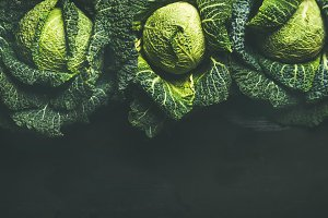 Raw fresh uncooked green cabbage over dark background, top view