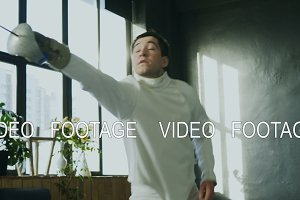 Young concentrated fencer man training fencing attack exercise in studio indoors