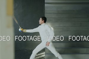 Young concentrated fencer man practice fencing exercises and training for competition in studio indoors