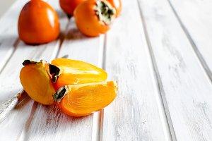 Ripe orange persimmons on an old woo