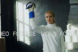 Tracking shot of Young concentrated fencer woman training fencing exercise in studio indoors