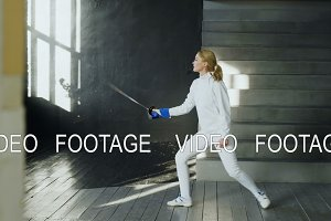 Young concentrated fencer woman practice fencing exercises and training for in studio indoors