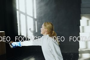 Young concentrated fencer woman training fencing attack exercise in studio indoors