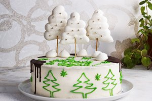 New Year cake with meringue trees and chocolate on a light background