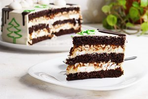 A cut of a New Year chocolate cake, a slice on a plate on a light background