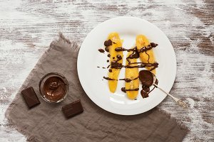Dessert roasted banana pour liquid chocolate served in a white plate, spoon in chocolate, rustic background.