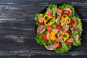Salad with bacon, tomatoes, grilled peppers and lettuce on a black plate.