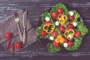 Greek salad on a black plate. Salad on a rustic background with a fork and knife. Toned photo