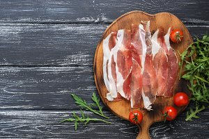 Sliced bacon on a cutting board, arugula, cherry tomatoes on a rustic dark background.