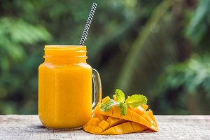Mango smoothie in a glass Mason jar and mango on a green background. Mango shake. Tropical fruit concept
