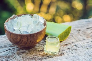 Slices of a aloe vera leaf and a bottle with transparent gel for medicinal purposes, skin treatment and cosmetics, close up