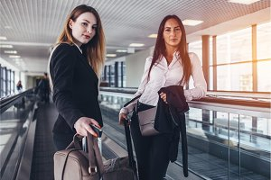 Two female business partners standing on moving walkway with heavy bags going to departure lounge