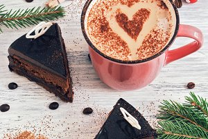 Coffee with heart and chocolate cakes on a white wooden table.