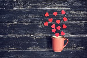 Pink cup on a wooden old background with red hearts. Valentine's Day. Photo with toning.