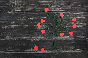 A green tree made from linen thread with red hearts instead of leaves on a wooden black background. Valentine's Day.