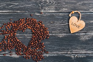 Heart of coffee beans on a wooden dark old surface. Wooden heart with text love. Top view with space