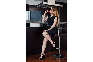 Beautiful sexy woman in a little black dress relaxing after shopping eating strawberry sitting on bar chair at home