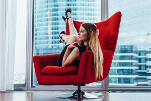 Sexy female model with fair hair posing on stylish red armchair against panoramic window with view of skyscrapers