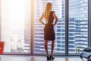 Rear view of elegant female boss standing in modern office looking at skyscrapers through the window